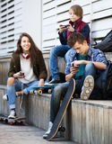 Teenagers with mobile phones. Teenage males and girl relaxing with cell phones on the street Stock Images