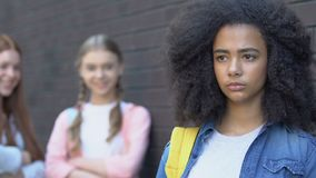 Teenagers mocking insecure biracial girl, gossiping about new classmate bullying. Stock footage stock video