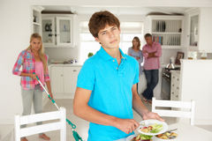 Teenagers not enjoying housework. Whilst parents watch Stock Photo