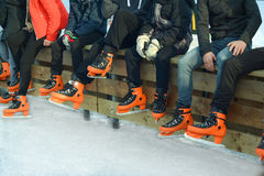 Teenagers in orange skate. On the ice stock images