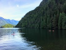 Teenagers paddle boarding and kayaking on a beautiful evening, in a remote inlet in British Columbia. stock photo