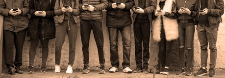 Teenagers with phones against wall. Group of teenagers with cell phones standing in front of wall and texting royalty free stock photography