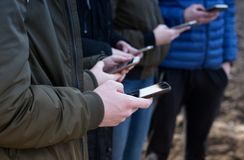 Teenagers with phones. Group of teenagers with cell phones texting in same time royalty free stock image