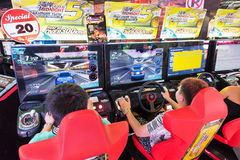 Teenagers play in amusement arcade, Bangkok Stock Images