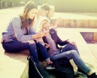 Teenagers play in smartphones in schoolyard royalty free stock photography