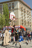 Teenagers play streetball on the open-air asphalt ground Stock Images