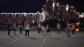 Teenagers play volleyball in the middle of a big night city. Evening lights