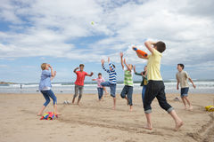Teenagers playing baseball on beach Stock Photography