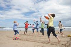 Teenagers playing baseball on beach Stock Photography