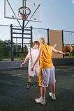 Teenagers playing basketball Stock Images