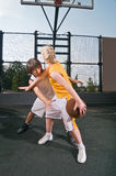 Teenagers playing basketball Stock Photos