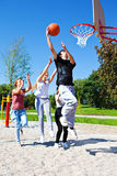 Teenagers playing basketball. Group of teenagers playing street basketball Royalty Free Stock Image