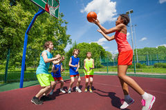 Teenagers are playing basketball game on ground Stock Photos