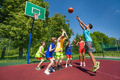 Teenagers playing basketball game together. On the playground during sunny summer day Stock Image