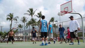 Teenagers playing basketball stock footage