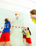 Teenagers playing basketball in sports hall Royalty Free Stock Photos