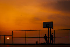 Teenagers playing basketball Stock Photography