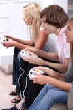 Teenagers playing computer games Stock Images