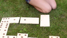 Couple playing giant dominoes on grass, close-up. stock video footage