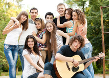 Teenagers playing guitar and singing stock image