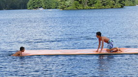 Teenagers Playing on a Long Floating Foam Pad on the Water Stock Photos