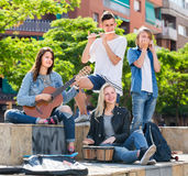 Teenagers playing music outdoors. Portrait of cheerful smiling teenage band playing music together outdoors Royalty Free Stock Photo