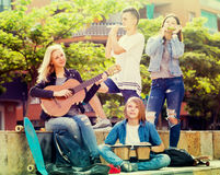 Teenagers playing music outdoors Stock Image