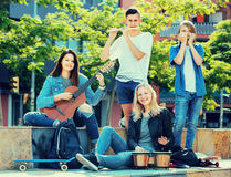 Teenagers playing music outdoors Stock Photos