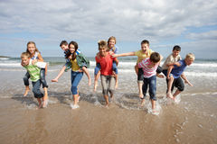 Teenagers playing piggyback. On the beach Royalty Free Stock Photo