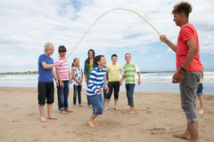 Teenagers playing skipping rope Stock Images