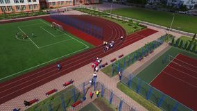 Teenagers playing on soccer field in school yard. Aerial view of sport ground stock video footage