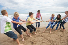 Teenagers playing tug of war. On beach royalty free stock photos