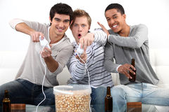 Teenagers playing video games. Three male teenagers playing video games Stock Photos