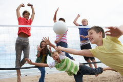 Teenagers playing volleyball. On beach royalty free stock images