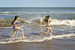 Teenagers playing with water. Two teenagers playing with the water, splashing and laughing in a beach of Mar del PLata, Argentina Stock Image