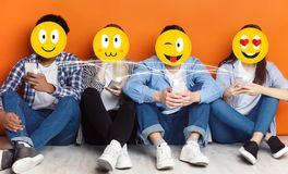 Teenagers with positive emoji icons using smartphones. And chatting in social networks, orange background stock photos