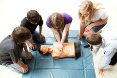 Teenagers Practice CPR. Teenage students use a mannequin to practice life saving techniques Royalty Free Stock Photo