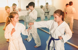 Teenagers practicing new karate moves in pairs in class Royalty Free Stock Image
