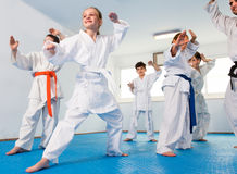 Teenagers are practicing new technique by repeating for the trai. Ner in karate class Royalty Free Stock Image