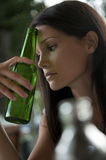 Teenagers problems. Beautiful young woman with a bottle of beer, looking depressed. Concept: teenagers and alcohol, teeneagers problems Royalty Free Stock Photos