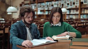 Teenagers Read Together. Two intellectual teenagers are reading together, discussing information as turning the pages, lovely long-haired girl wearing green stock video