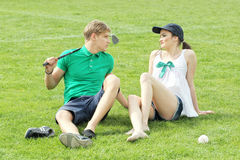Teenagers relaxing on a green grass field. Sunny day Stock Image