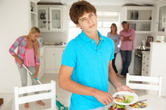 Teenagers reluctantly doing housework. Looking at camera Stock Photography