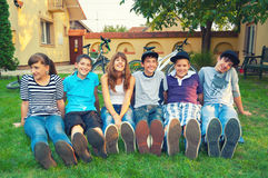 Teenagers resting on the grass after bicycle ride Royalty Free Stock Photos