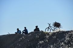 3 teenagers resting on a hill in a rural area with a bike loaded with fire wood. Garas, Keetmanshoop / Namibia - July 15 2017 :Cool day in the sun, Three stock photo