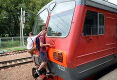 Free Teenagers Ride Without Payment On The Exterior Of The Tail Car Of The Train And Passengers On The Railroad Tracks Stock Image - 113850751