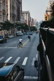 Teenagers riding bikes on the road in Harlem, New York, USA. New York, USA - June 1, 2018: Teenagers riding bikes on the road in Harlem, New York. Since the royalty free stock image