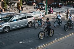 Teenagers riding bikes on the road in Harlem, New York, USA. New York, USA - June 1, 2018: Teenagers riding bikes on the road in Harlem, New York. Since the royalty free stock photo