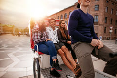 Teenagers riding on tricycle and having fun Royalty Free Stock Image