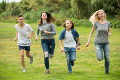 Teenagers running on green lawn in park Royalty Free Stock Photography